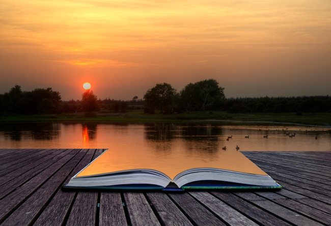Creative concept of beautiful simple image of sunset through tress reflected in lake in foreground coming out of magical book laid open